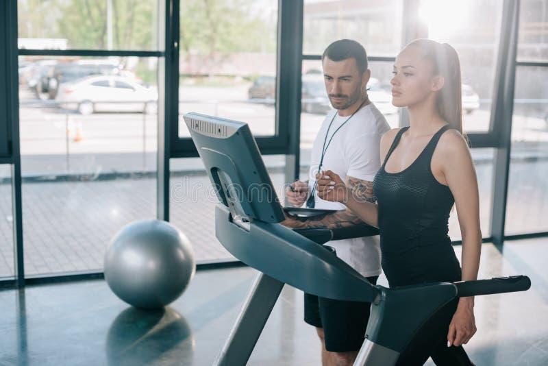 mannelijke persoonlijke trainer die het tredmolenscherm bekijken terwijl sportvrouw stock fotografie