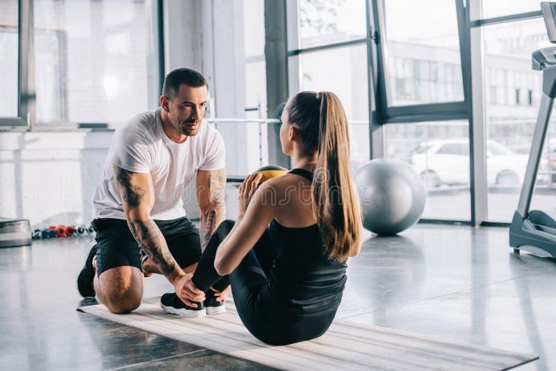 mannelijke persoonlijke trainer die sportvrouw helpen stock afbeeldingen