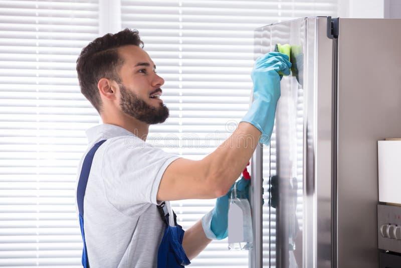 Mannelijke Portier Cleaning Refrigerator stock afbeelding