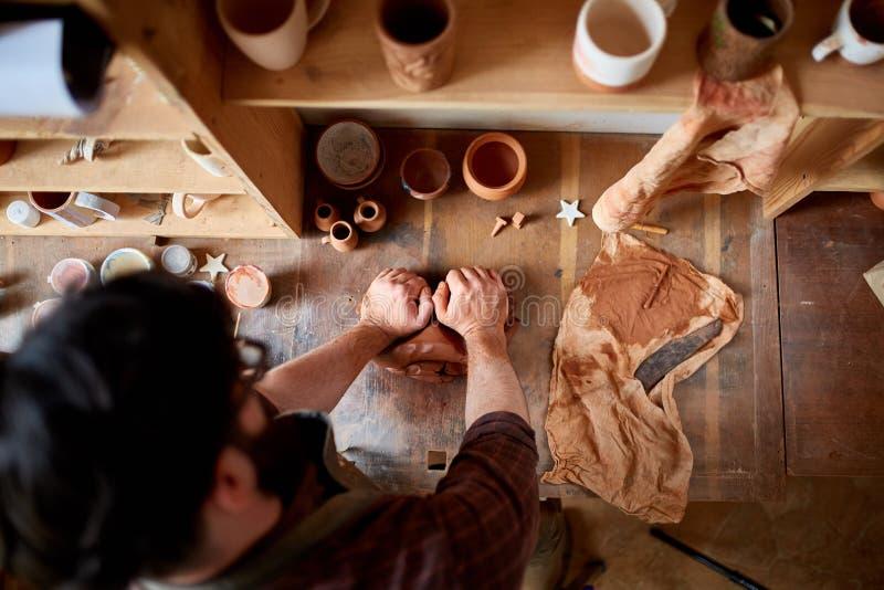 Mannelijke pottenbakker die een klei in aardewerkworkshop vormen, close-up, selectieve nadruk royalty-vrije stock afbeeldingen