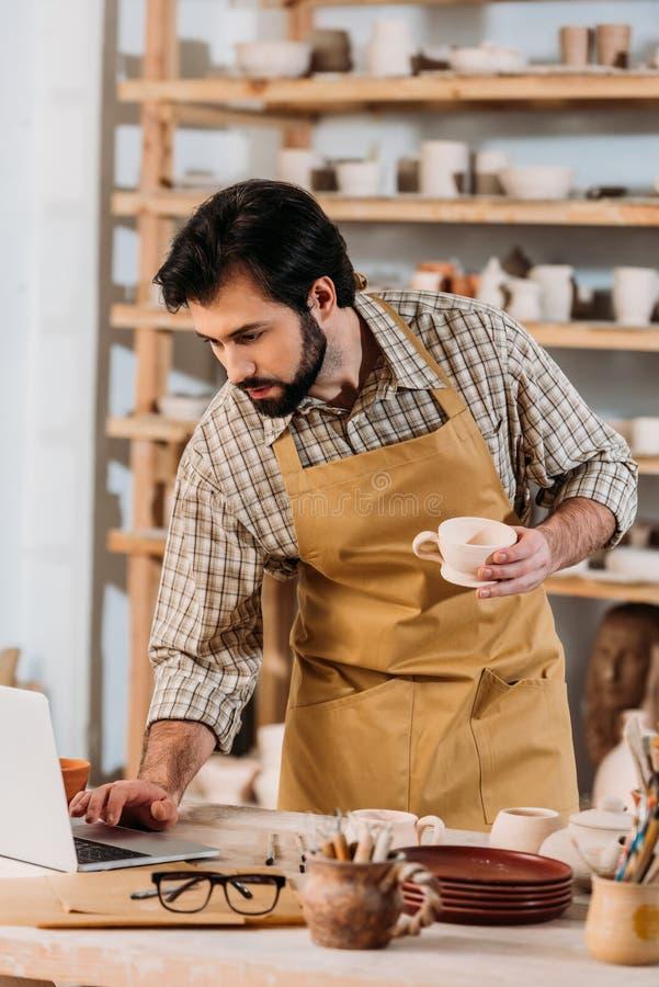mannelijke pottenbakker in schort die ceramische kop houden en laptop met behulp van stock afbeeldingen