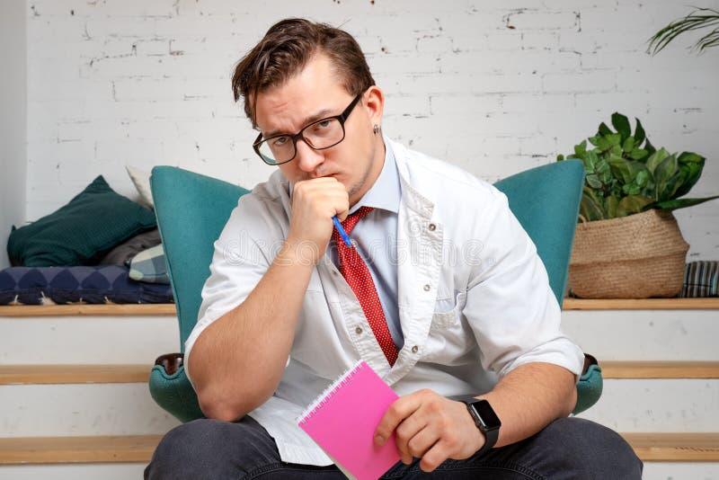 Mannelijke psychiater met potlood en klembord die sullenly de camera onderzoeken, die aan de klachten van de patiënt luisteren royalty-vrije stock foto