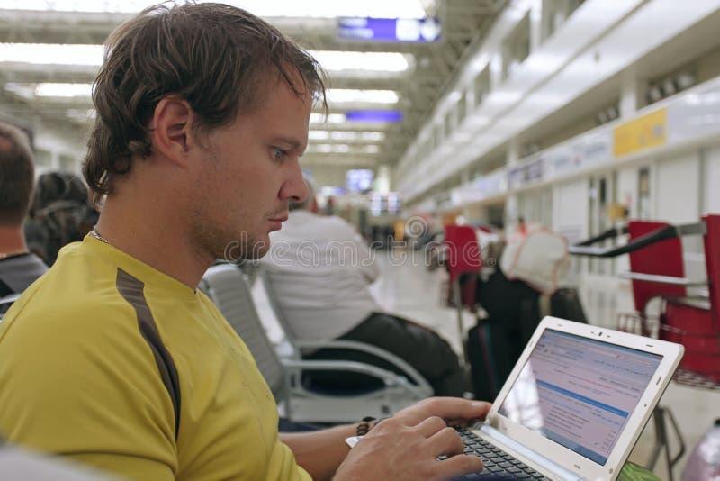 Mannelijke reiziger die aan zijn laptop computer werkt royalty-vrije stock fotografie