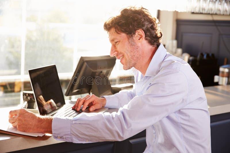 Mannelijke restaurantmanager die aan laptop werken stock afbeelding