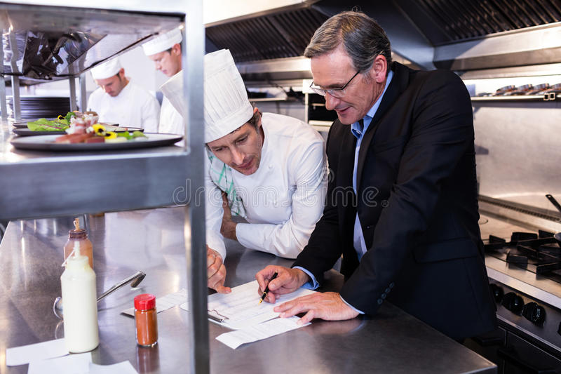 Mannelijke restaurantmanager die op klembord schrijven terwijl het op elkaar inwerken aan hoofdchef-kok royalty-vrije stock foto
