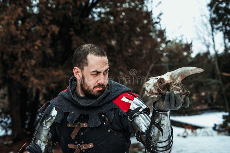 Mannelijke ridder die een schedel in zijn hand houden royalty-vrije stock afbeelding