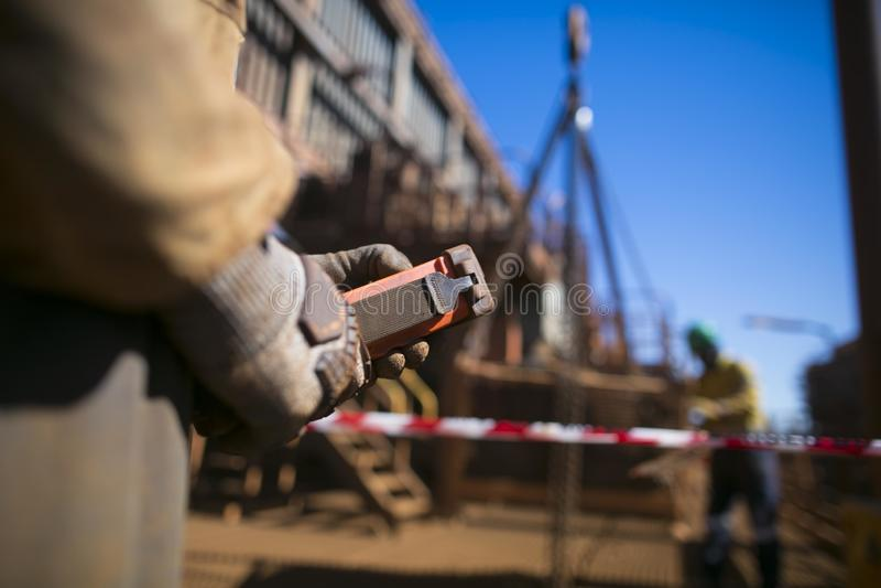 Mannelijke riggerhand die de rode verre opheffende lading controleren van de hijstoestelkraan terwijl onscherp beeld van zijn hol stock foto's