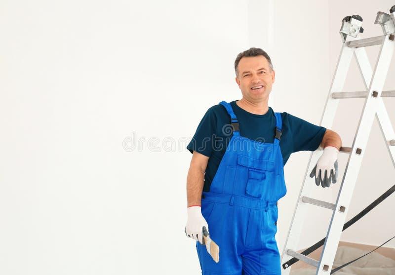 Mannelijke schilder in eenvormig met borstel dichtbij ladder binnen stock afbeelding