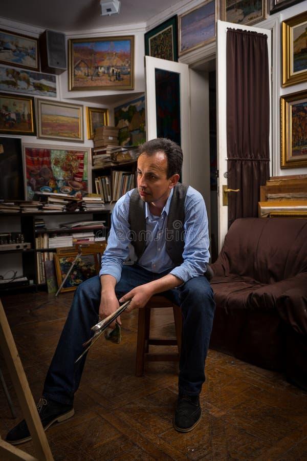 Mannelijke schilderszitting die in een studio denken royalty-vrije stock foto's