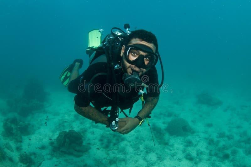 Mannelijke scuba-duiker die over ertsader zwemt royalty-vrije stock fotografie