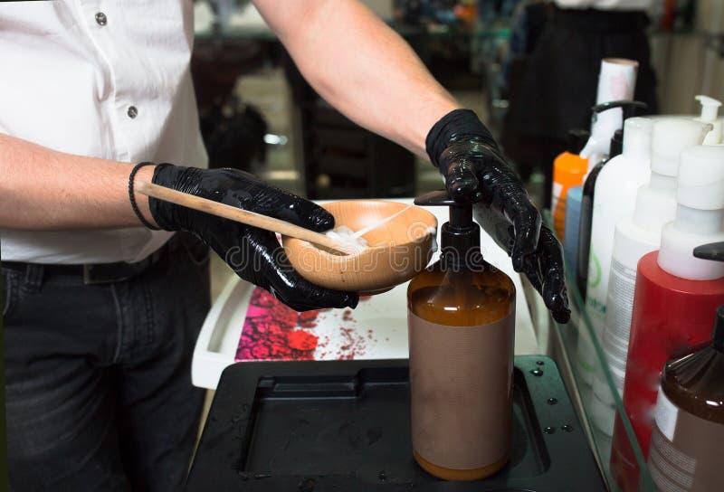 Mannelijke Stilist die in handschoenen kleurenroom voor het sterven haarcontainer, een masker voor behandelingsprocedure voorbere royalty-vrije stock afbeeldingen