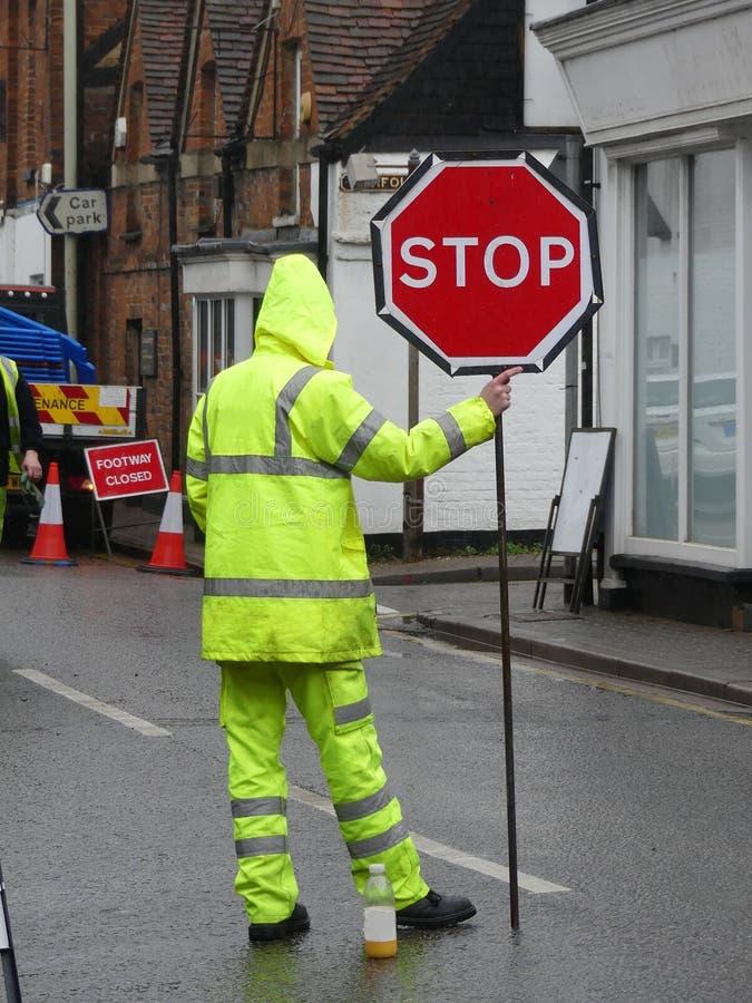 Mannelijke stratemaker met geel fluorescent jasje en broeken die einde rood teken houden stock afbeeldingen