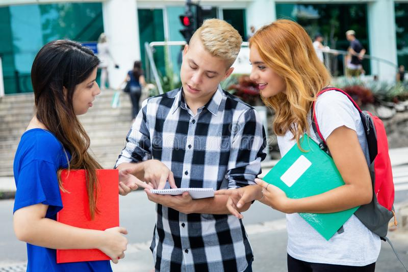 Mannelijke student in bespreking met Kaukasische vrouwelijke studenten royalty-vrije stock afbeelding