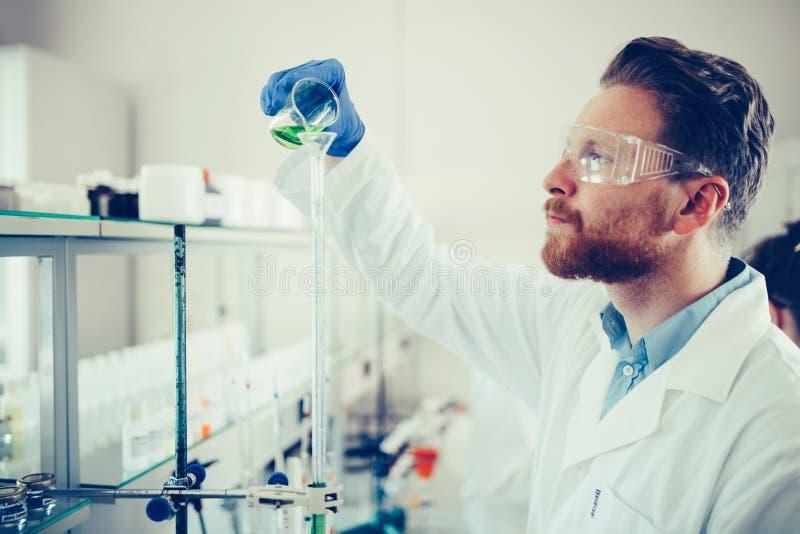 Mannelijke student die chemie in laboratorium werken stock afbeeldingen