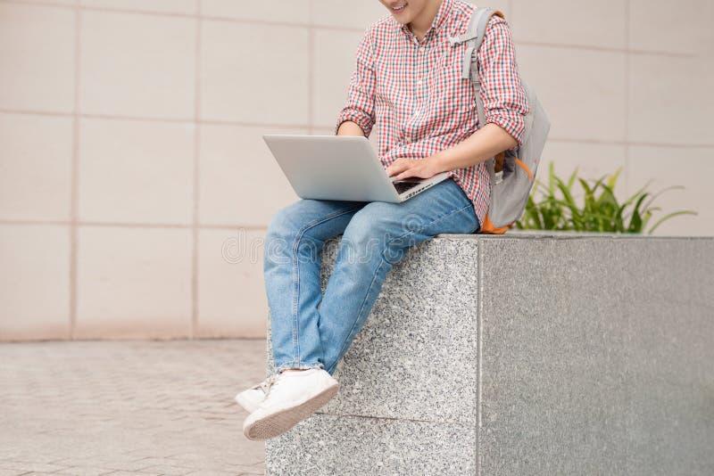 Mannelijke student die laptop in universiteitscampus met behulp van stock foto