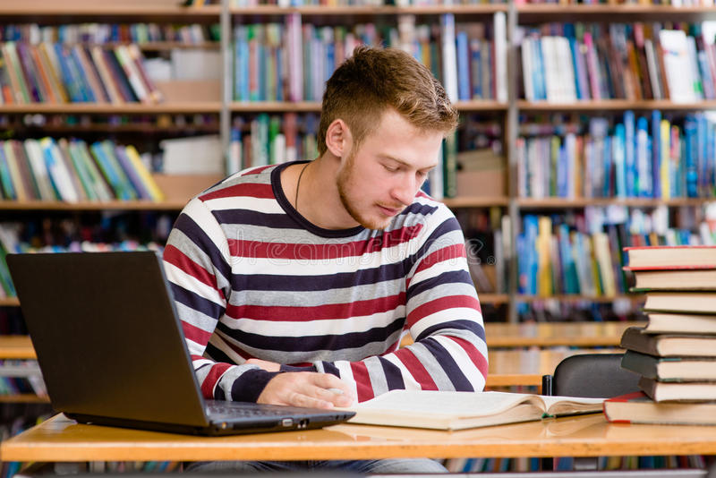 Mannelijke student die met laptop in de universitaire bibliotheek bestuderen stock foto