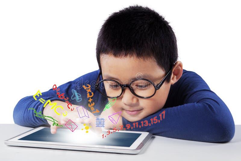 Mannelijke student die met tablet op bureau bestuderen stock fotografie