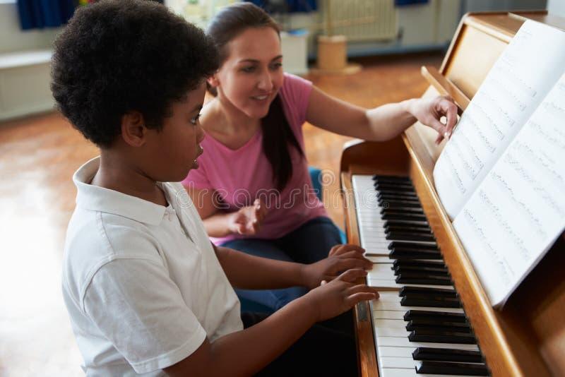 Mannelijke Student Enjoying Piano Lesson met Leraar stock foto