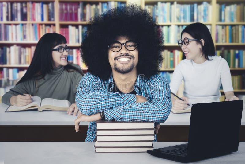Mannelijke student met zijn vrienden in de bibliotheek stock fotografie