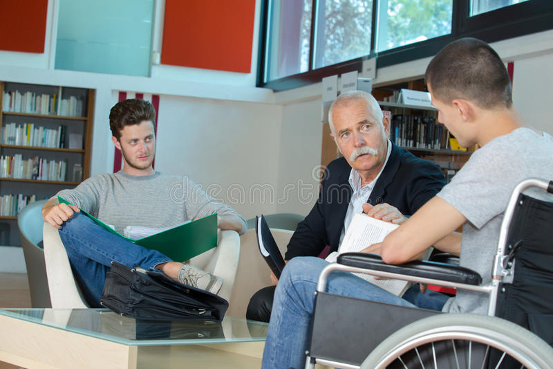Mannelijke student in rolstoel bij teller in universiteitsbibliotheek stock afbeeldingen