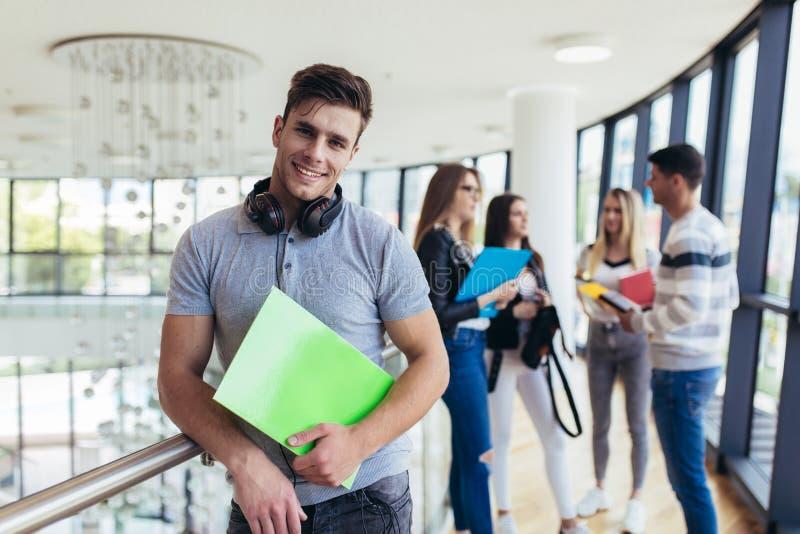 Mannelijke studenten bevindende muur in gang van een universiteit Kaukasische mannelijke student in universitaire campus stock foto's