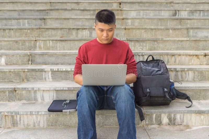 Mannelijke studentenzitting op tredestappen, die laptop met behulp van royalty-vrije stock fotografie