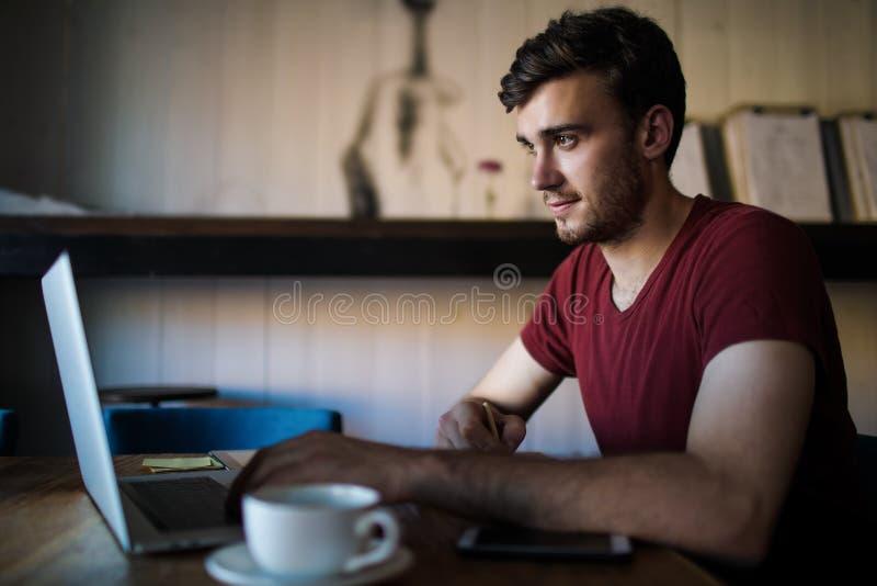 Mannelijke succesvolle tekstschrijver die een artikel voor publicatie voorbereiden die netbook gebruiken royalty-vrije stock afbeeldingen