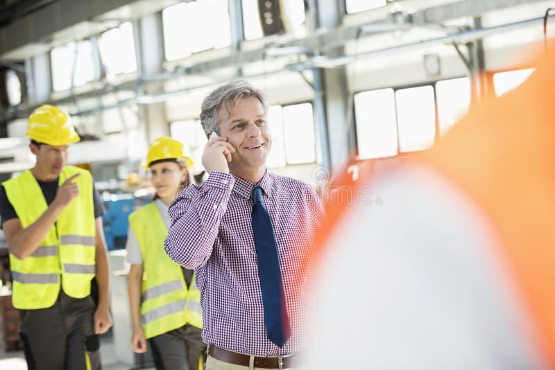 Mannelijke supervisor die op mobiele telefoon met arbeiders op achtergrond bij de industrie spreken stock fotografie