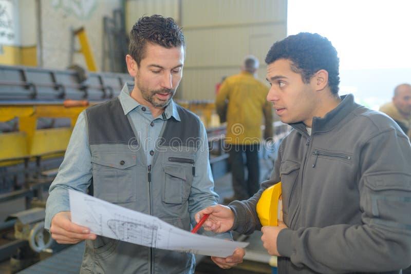 Mannelijke supervisor met arbeider het bespreken over blauwdrukken in de industrie royalty-vrije stock afbeeldingen