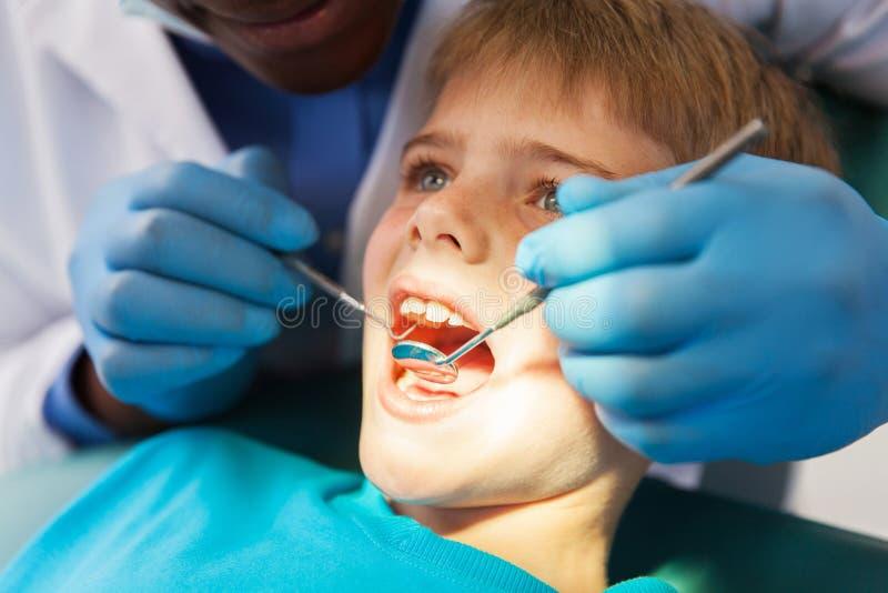 Mannelijke tandarts die jongenstanden onderzoeken royalty-vrije stock afbeeldingen