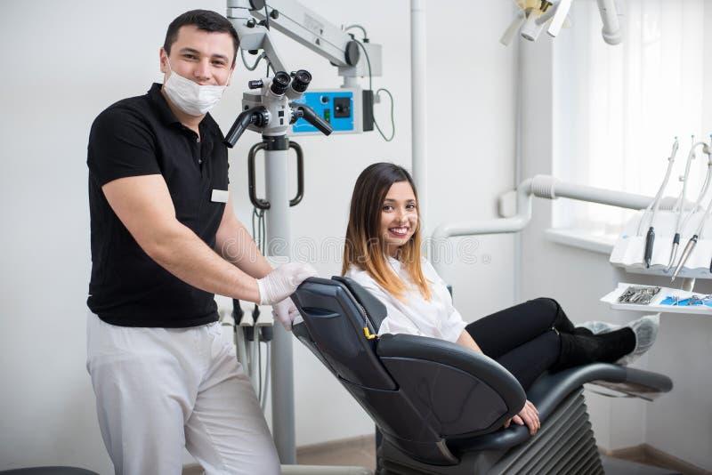 Mannelijke tandarts met mooie vrouwelijke patiënt na behandeling in moderne tandkliniek Vrouwenzitting als tandvoorzitter stock fotografie