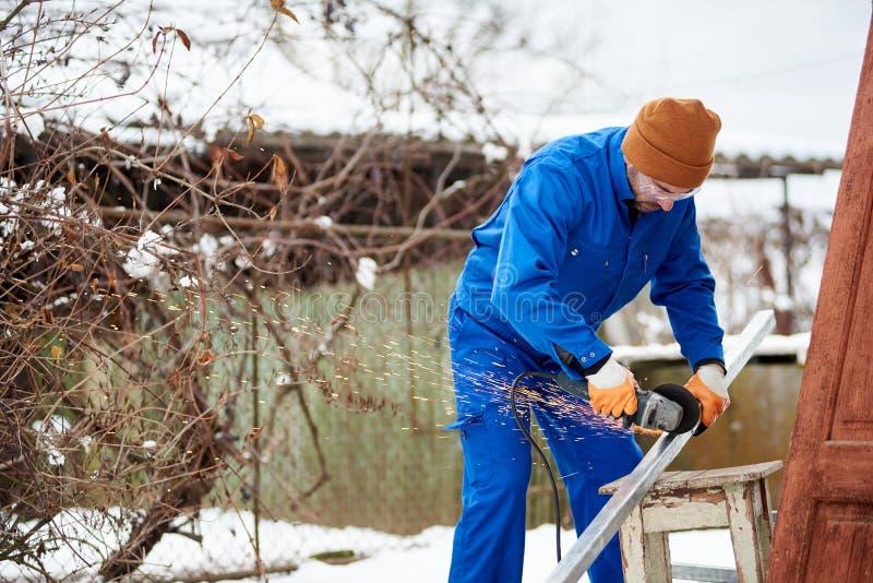 Mannelijke technicus in blauw kostuum scherp metaal met scherp wiel die klaar om photovoltaic zonnepanelen te installeren worden stock fotografie