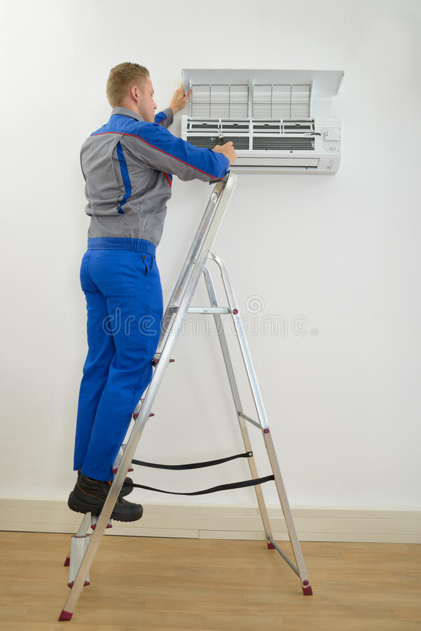 Mannelijke technicus die airconditioner herstellen stock fotografie
