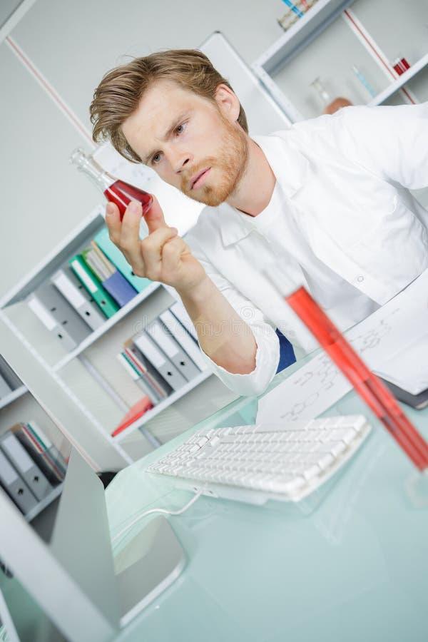 Mannelijke technicus die bloedmonster in medisch laboratorium analyseren stock fotografie