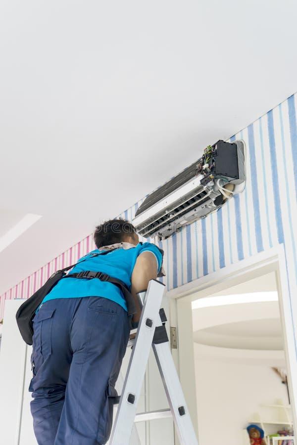 Mannelijke technicus die een airconditioner controleren royalty-vrije stock afbeeldingen