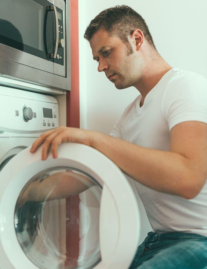 Mannelijke technicus die wasmachine herstellen royalty-vrije stock afbeeldingen