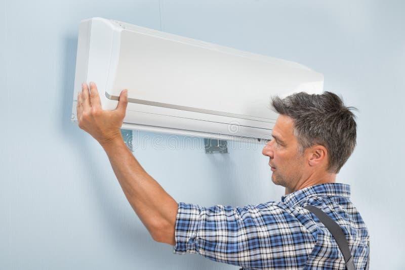 Mannelijke technicus het bevestigen airconditioner stock afbeeldingen