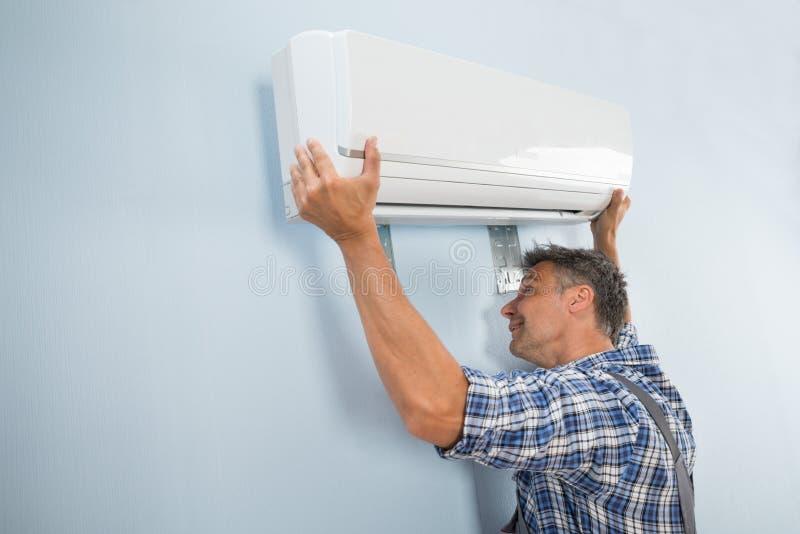 Mannelijke technicus het bevestigen airconditioner stock foto