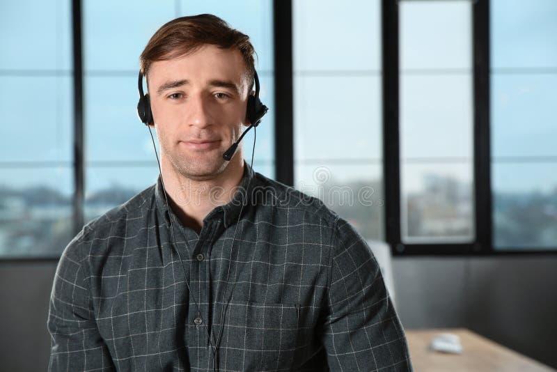 Mannelijke technische ondersteuningexploitant met hoofdtelefoon in bureau stock afbeeldingen