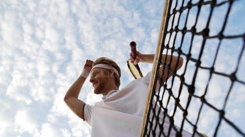 Mannelijke tennisspeler die van zijn overwinning genieten bij tenniskampioenschap, die handen opheffen stock afbeeldingen