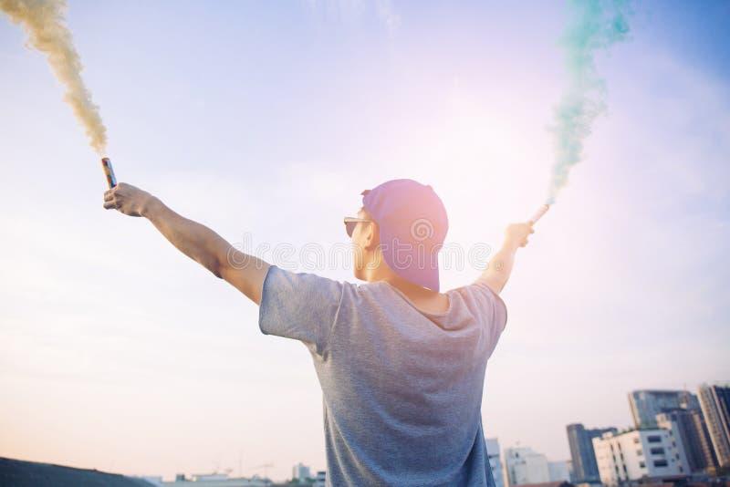 Mannelijke tiener die kleurrijke rookstokken in de lucht over stedelijke stadsachtergrond tegenhouden royalty-vrije stock afbeeldingen