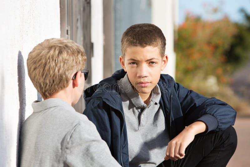 Mannelijke tiener die met ernstige uitdrukking aan vriend luisteren stock foto's