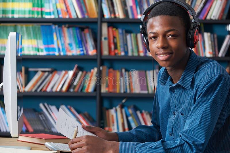 Mannelijke Tienerstudent Working At Computer die Hoofdtelefoons dragen stock afbeelding