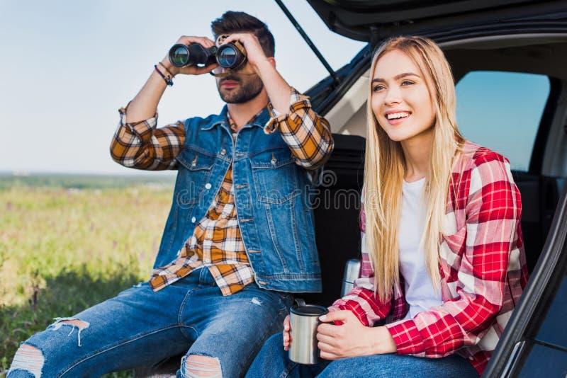 mannelijke toerist die door verrekijkers kijken terwijl zijn glimlachend meisje royalty-vrije stock fotografie