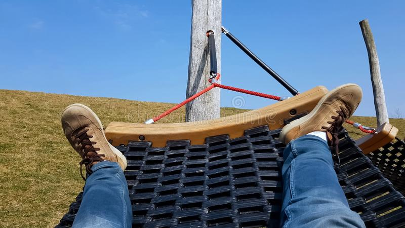 Mannelijke toerist die in hangmat, luie vrije tijd, verfrissing op vreedzame weide slingeren stock afbeelding