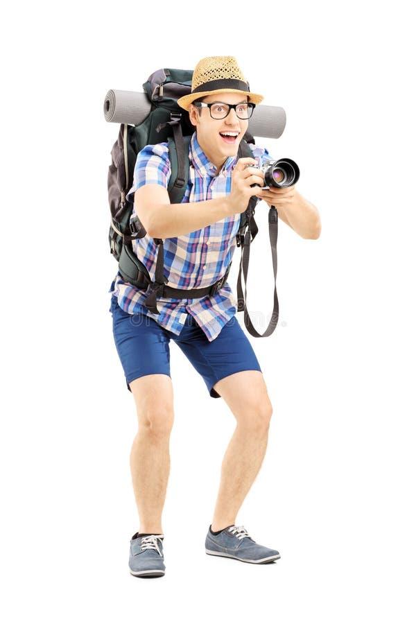 Mannelijke toerist met rugzak die een beeld met de camera nemen stock afbeelding