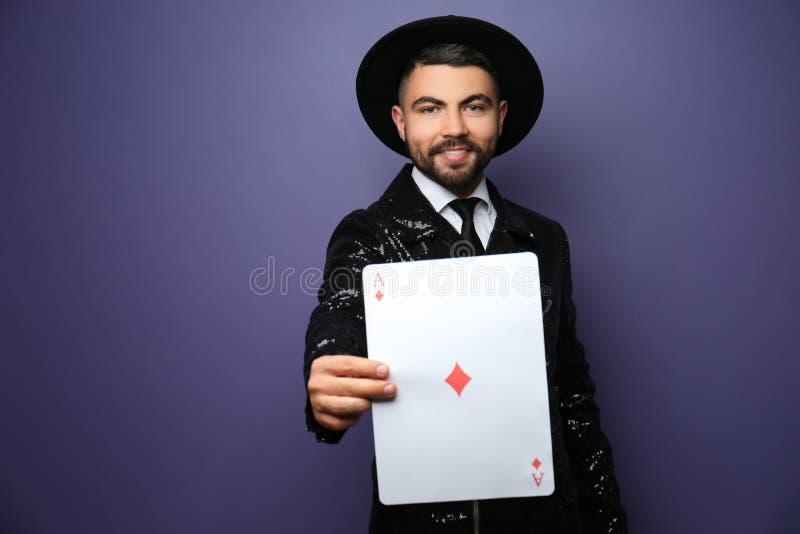 Mannelijke tovenaar die trucs met kaart op kleurenachtergrond tonen stock foto's
