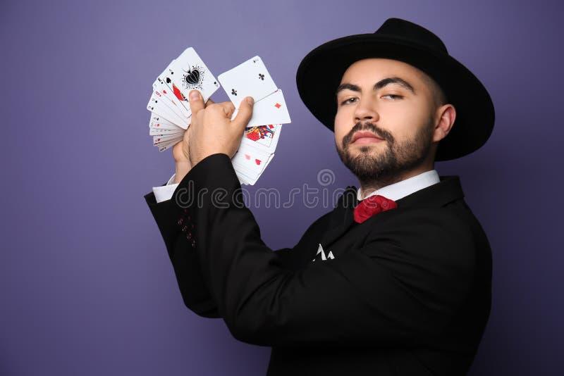 Mannelijke tovenaar die trucs met kaarten op kleurenachtergrond tonen stock afbeelding