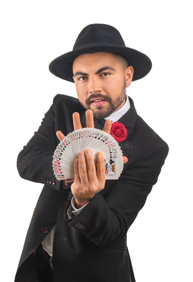 Mannelijke tovenaar die trucs met kaarten op witte achtergrond tonen royalty-vrije stock foto