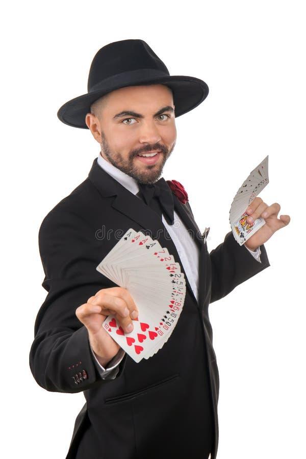 Mannelijke tovenaar die trucs met kaarten op witte achtergrond tonen stock foto's